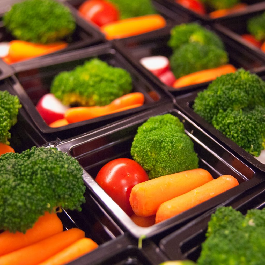 Broccoli, baby carrots, and cherry tomatoes prepared for healthy school lunch.