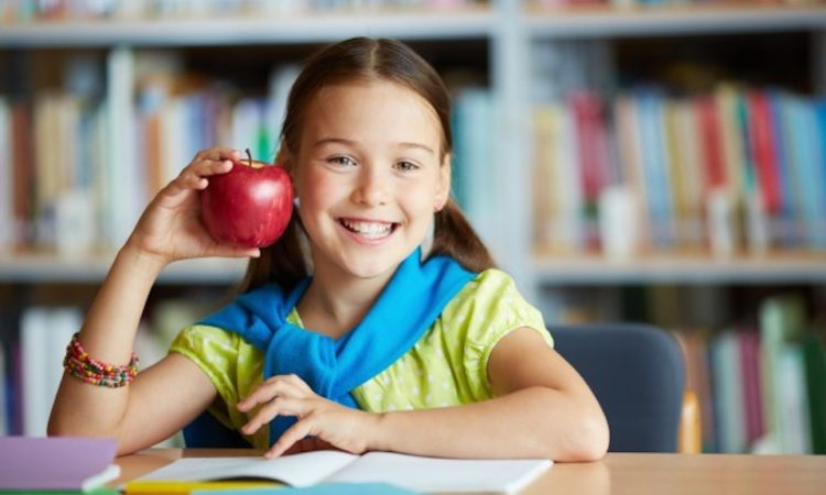Girl smiling with apple