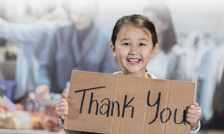 Smiling girl in a school cafeteria holding a cardboard Thank You sign