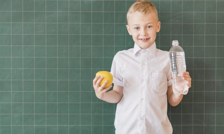 Junior with water apple near chalkboard